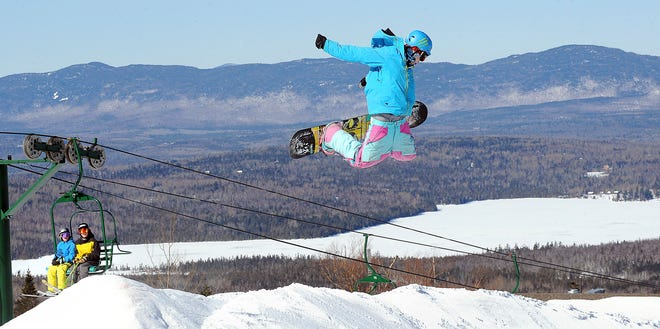 A snowboarder flies over a jump at Saddleback Mountain  in Rangeley, Maine, in a 2011 photo. Saddleback Mountain reopened after a five-year hiatus with revamped lodge, a new chairlift and changes in the lodge aimed at making skiing safer.