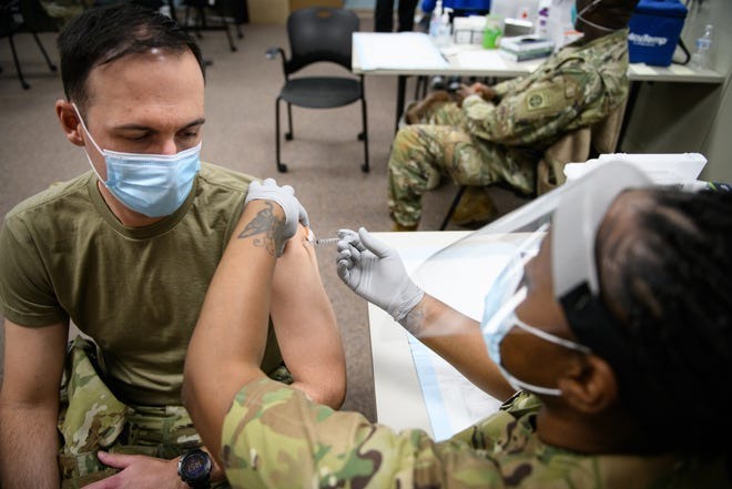 Sgt. Paula Smith, right, gives Maj. Nathan Wagner the Pfizer-BioNTech COVID-19 vaccine at Womack Army Medical Center on Thursday.