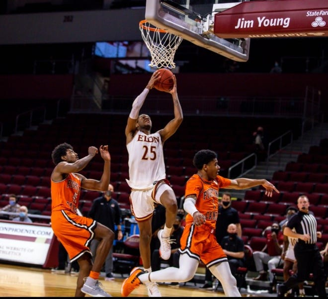 Elon's Hunter Woods takes off between Campbell's Cedric Henderson Jr., left, and Ricky Clemons, right, during Wednesday's game at Schar Center.