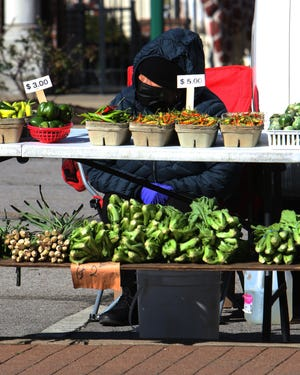 A vendor waits on customers at the Downtown Fort Smith Farmer's Market on Garrison Avenue.