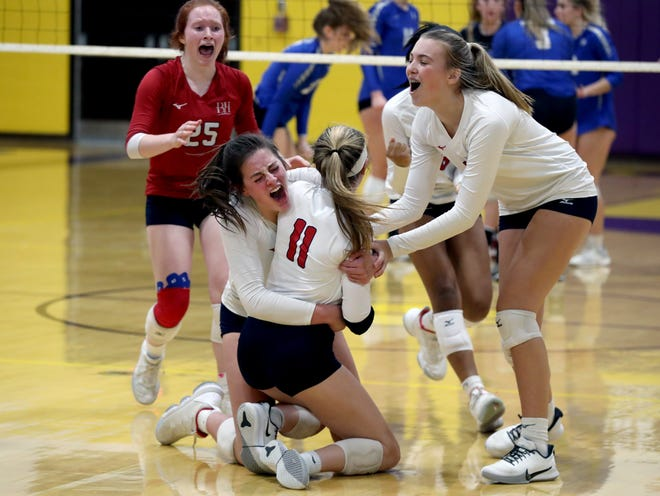 Hartley's Ella Brandewie hugs teammate Colleen Sweeney (11) as Lauren Johnson (25) and Kaylee Musick (8) race to join in after Hartley beat Gilmour Academy in the third game of their Division II regional semifinal Nov. 5 in Lexington. The Hawks lost the match in five games.