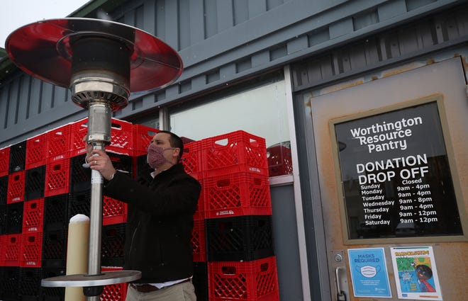 Executive director Nick Linkenhoker assembles an outdoor heater to help keep volunteers warm at the Worthington Resource Pantry on Dec. 16. The food pantry is one of the grant recipients in a new Worthington program that uses federal CARES Act funding.