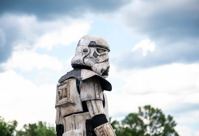 "Nick Fox, portrays a Star Wars Stormtrooper as he watches vehicles drive through the ""Star Wars Droid Checkpoint"" food drive July 11 at Civic Park."
