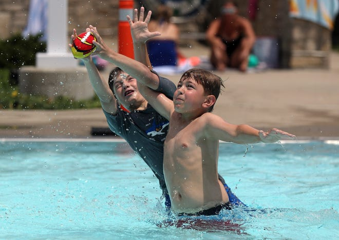 Owen Dick, left, 10, and Thomas Dury, 10, both of Upper Arlington, battle for a ball June 16 at Tremont Pool. The city opened the pool with a modified schedule and safety protocols in response to the COVID-19 coronavirus pandemic.