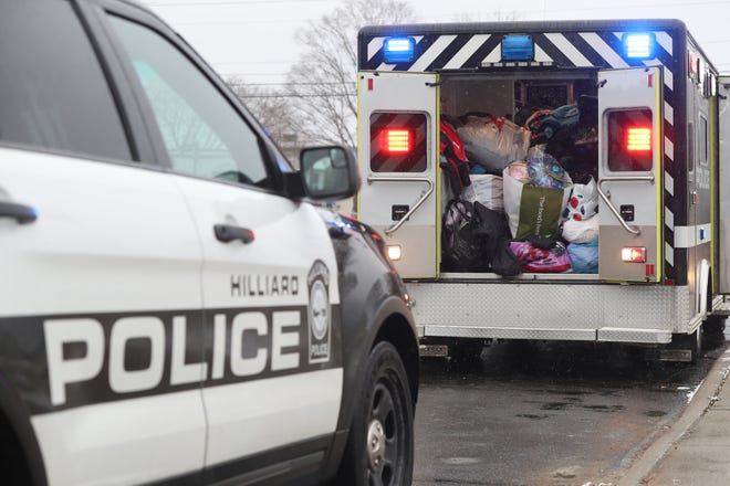 Bags full of donated winter clothing for students in need fill the back of a Hilliard Division of Police vehicle before being taken inside Hilliard City Schools' Beacon Elementary School on Dec. 16. The items were collected as part of the police division's annual Cram the Cruiser drive.