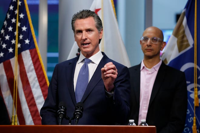 In this March 17, 2020, file photo California Health and Human Services Agency Director Dr. Mark Ghal, right, looks on as California Gov. Gavin Newsom talks at a news conference at the Governor's Office of Emergency Services in Rancho Cordova.