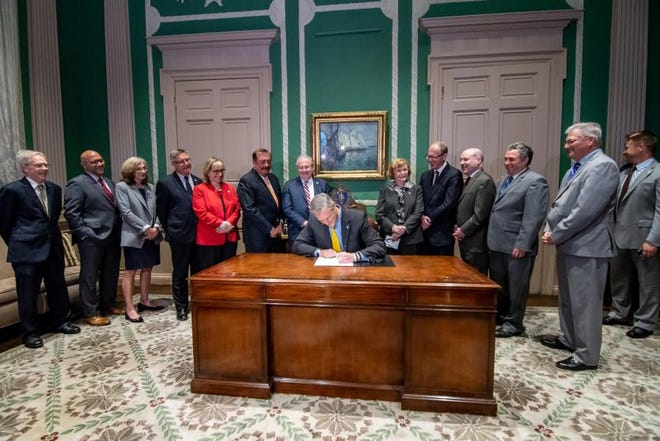 Gov. Charlie Baker signs a bill into law in June of 2018 establishing Massachusetts' paid family and medical leave.