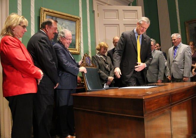 Gov. Charlie Baker takes a seat to sign 'the grand bargain' legislation in June of 2018.