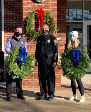 Walter Fust, left, National Honor Society co-advisor at Plymouth South High School and PSHS senior Kasey McPherson deliver holiday wreaths to Police Chief Michael Botieri last week.