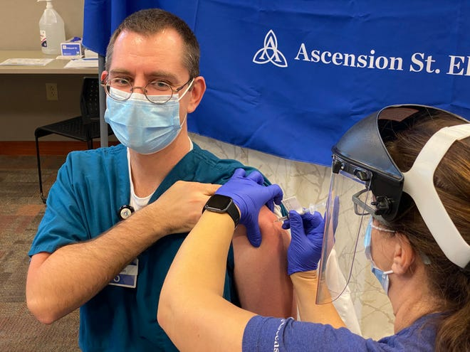 Dr. Anthony Zeimet, an infectious diseases specialist who treats COVID-19 patients at Ascension St. Elizabeth in Appleton and via telemedicine at Mercy Hospital in Oshkosh, receives the area's first COVID-19 vaccine Thursday afternoon.