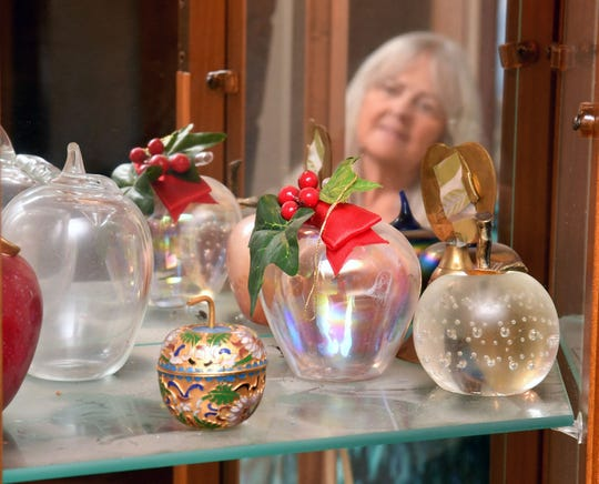 Sally Munson, of Cordova, looks over some of the 273 apples made of glass, ceramic or metal that have been given to her mother, Eleanor Moody Pettit. A former teacher, Eleanor, 99, recently died of COVID-19.