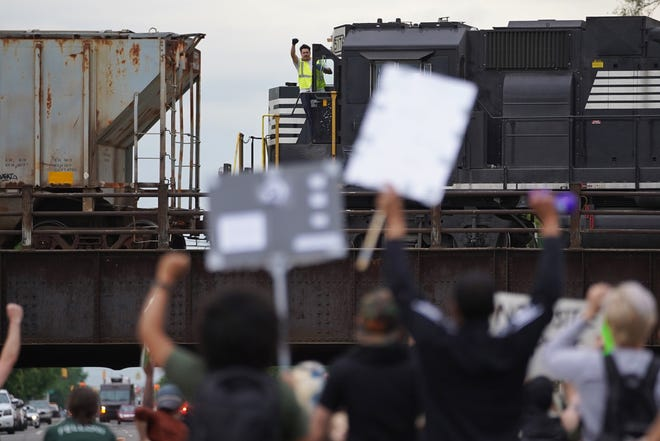 A man raises his hand in solidarity from a train as protesters walk through Southwest Detroit on Monday, June 1, 2020 for the fourth day of protesting in the city.