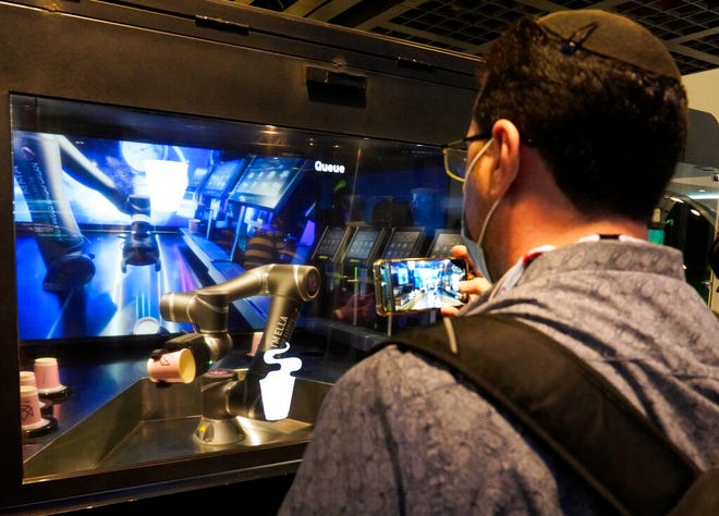 Seorang pria Israel memfilmkan robot saat membuatnya secangkir kopi di KTT teknologi GITEX di Dubai, Uni Emirat Arab, Senin, 7 Desember 2020.