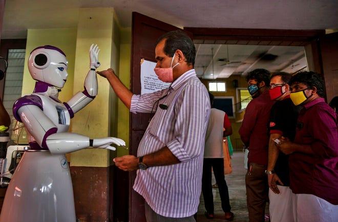 Robot memeriksa suhu dan menawarkan pembersih kepada orang-orang yang datang untuk memilih pemilihan badan lokal di Kochi, negara bagian Kerala, India, Kamis, 10 Desember 2020.