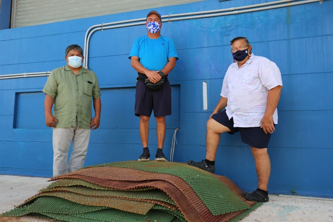 "The Guam Football Association recently donated outdoor rubber mats to the Yigo Mayor's Office for use at village facilities and events. From left: GFA President Tino San Gil; Tony Sanchez, Yigo vice mayor and mayor-elect; and GFA General Secretary Marvin ""Ike"" Iseke are shown in this photo taken Dec. 15 in Yigo."