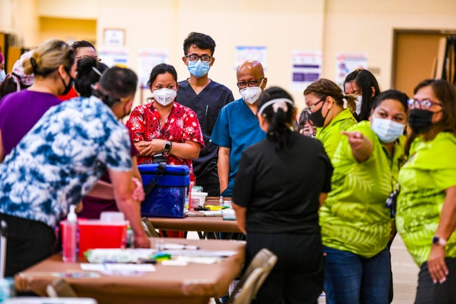 Department of Public Health and Social Services workers and other health professionals gather for last minute instructions prior to administering the first round of the Pfizer-BioNTech COVID-19 vaccine during a temporary clinic established within the Okkodo High School on Thursday, Dec. 17, 2020.