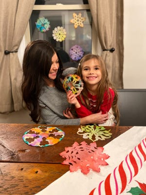 Shelbyville, Ind., Realtor and crafty mom Becky Allen and her daughter, Stella Mink, are shown with their colorful coffee filter Make-A-Flake snowflakes at their home on Wednesday, Dec. 16, 2020.