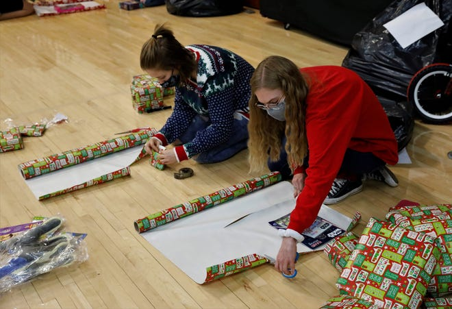 Millersport High School seniors Emma Diyanni, left, and Aimee Foltz wrap gifts as part of the annual White Christmas Project. This year, the project will provide 25 families in need with gifts and food for Christmas.