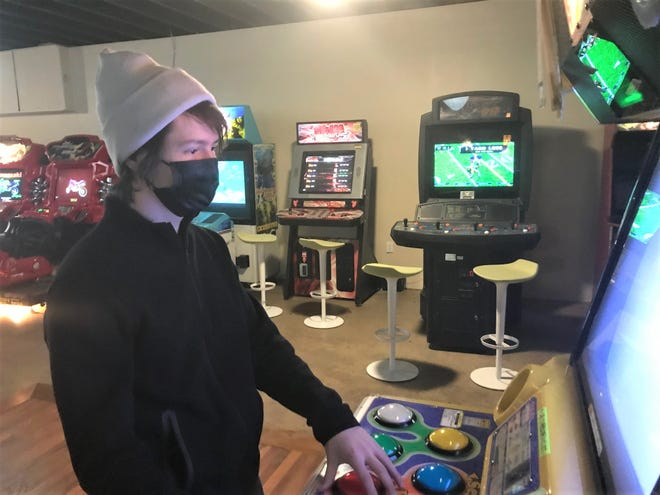 Bunker Arcade co-owner George Locke plays one of the 55 or so machines in the new business he opened with Shane Mack