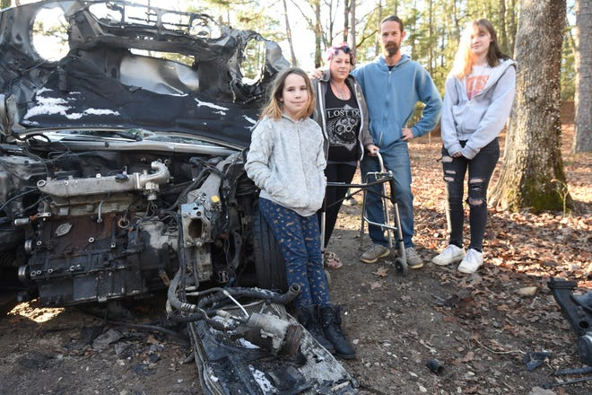 Daisy Henson, second from left, was seriously injured in a September car accident that broke both her legs and shattered more than 50 bones in her right leg and foot. She is home now recovering with the help of her husband Jeremy, second from right, her younger daughter Juniper, left and older daughter Joni. The family stands next to the 2003 MINI Cooper Daisy was driving when a truck pulled into her path.