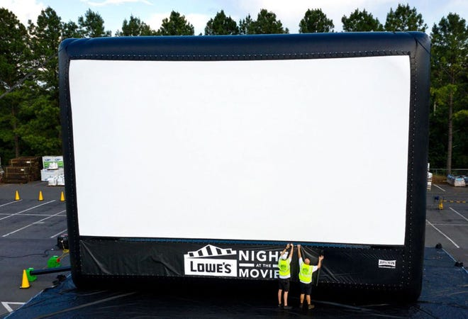 Staff sets up a Lowe's Night at the Movies screen at a Lowe's in Charlotte, N.C. this summer.