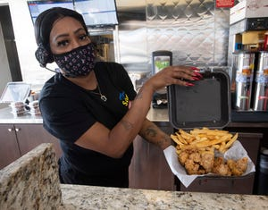 Sam's Seafood & Grill employee Juliette Savage shows off one of the restaurant's fried seafood dinners Dec. 17, 2020.