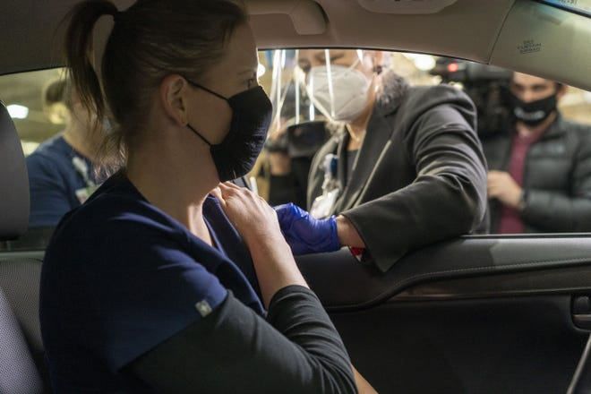 Banner Health nurse Emily Beck gets a COVID-19 vaccination from Dr. Marjorie Bessel at Arizona State Fairgrounds in Phoenix, on Dec. 17, 2020.