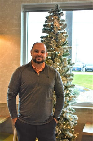 Genoa McDonald's owner/operator Matthew MacKenzie stands next to the Christmas tree that former General Manager Roland Lopez decorated for years at the restaurant. Lopez died in May, so two employees decorated the restaurant in his honor.