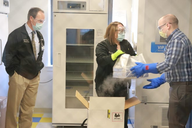 From left to right: Todd Fry, director of WellSpan Pharmacies, Amanda Nonemaker, pharmacies buyer, and Brent Carpenter, manager of procurement, unbox WellSpan York Hospital's first delivery of COVID-19 vaccines.
