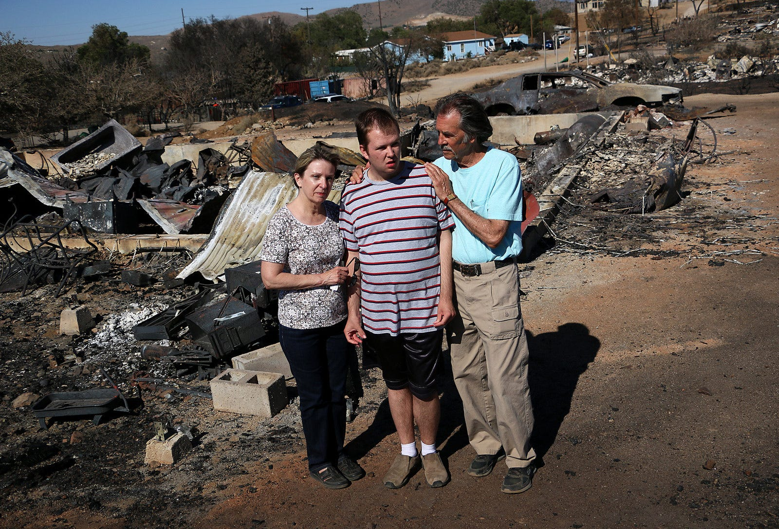 John Ranger, right, stands with his wife Nancy and son Brogan at the site of their home that burned during the Poeville Fire near Reno on July 3, 2020.