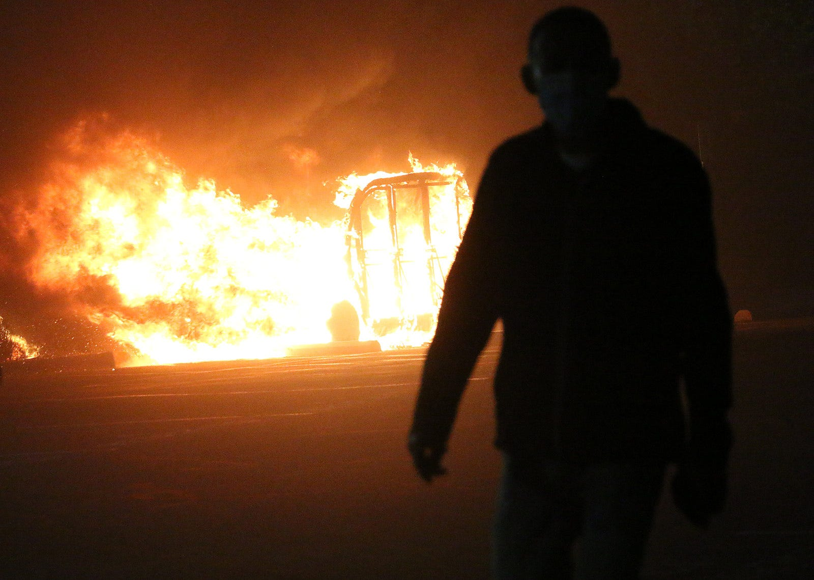 A protester walks in front of a burning vehicle during the Black Lives Matter rally and civil unrest in Reno on May 30, 2020.
