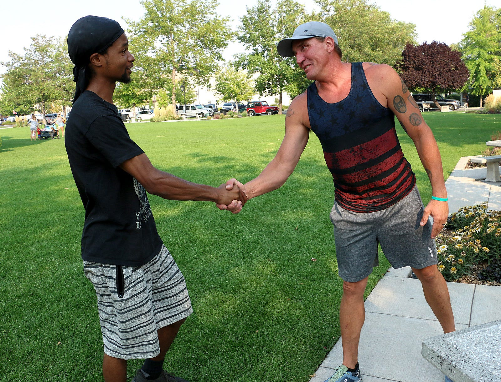 Jerome Silas, left, and Brian Johnson shake hands while meeting in Minden Park in Minden on Aug. 25, 2020. A striking image was taken of Silas and Johnson during a Black Lives Matter protest that attracted about 50 supporters and more than 1,500 counter-protesters in Minden Aug. 8. The two fathers from Northern Nevada were from opposite sides of a conflict with the same goal: to protect their community. The RGJ invited them to meet and talk about the experience and the impact that moment, and that day, had on them.