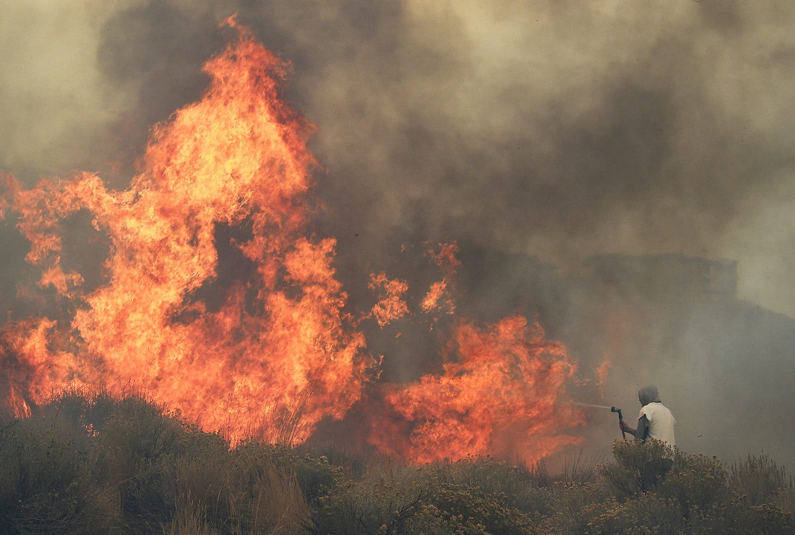 Homeowner Steven Phelps battles the Pinehaven Fire in the Caughlin Ranch area of Reno on Nov. 17, 2020.