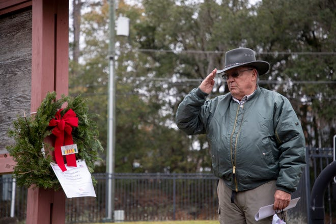David Wilson salutes a wreath hanging at the entrance of Greenwood Cemetery in honor of three veterans buried there in unmarked graves Thursday, Dec. 17, 2020.