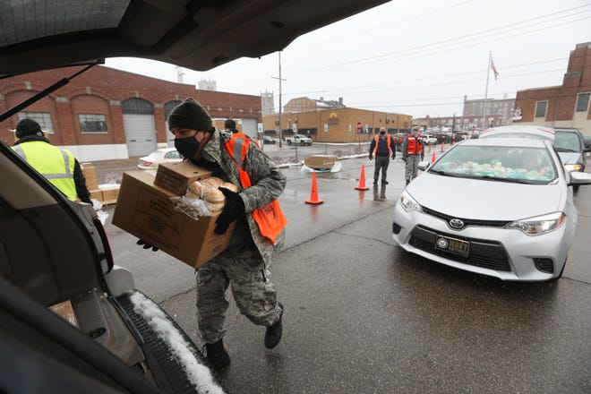 Major Joseph Mosher, unit commander of the OH-085 squadron in the Ohio Wing of Civil Air Patrol, loads a vehicle with one of the food boxes distributed outside Secrest Auditorium in Zanesville on Wednesday, December 16.