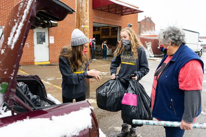 Kate Martin hands Addisyn Atkinson a bag of toys while Janice Campfield waits to add a roll of wrapping paper to the trunk of Karissa Lee's car.