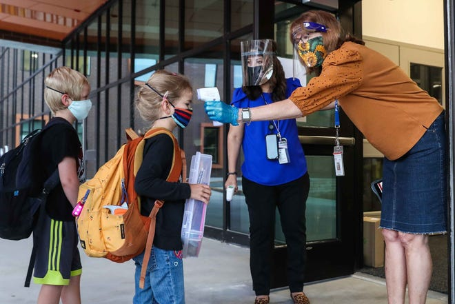 Patricia McKenze takes a student's temperature before entering to Doss Elementary School in Northwest Austin on Oct. 5, the first day of in-person classes this school year at the Austin school district. District officials are planning to eliminate positions because of revenue losses from declining enrollment.