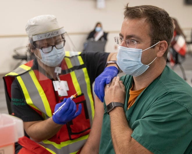 Dr. Michael Garcia, left, administers the Pfizer coronavirus vaccine to Dr. Nicholas Steinour at Dell Seton Medical Center at the University of Texas on Friday December 18, 2020.