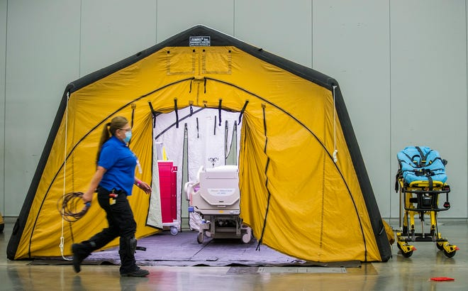 Austin Convention Center employee Sylvia Estrada walks past an empty patient bed at the Austin Convention Center in July, when coronavirus cases spiked. The convention center is preparing to take patients amid another surge of COVID-19 cases after the holidays.