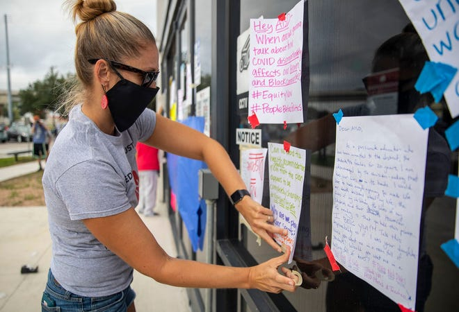 Elizabeth Mikeska-Benfield tapes a note on a window at Austin school district offices in September demanding safe work conditions. On Thursday, district board members approved $1,000 retention payments for most full-time and part-time employees.