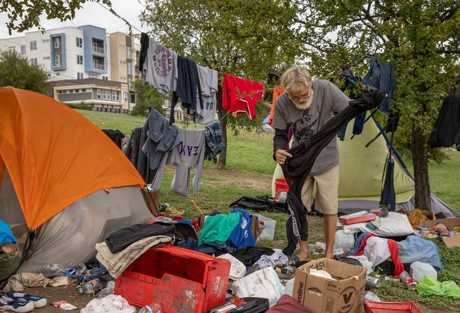 Martin Nelson is shown in September going through some of his belongings at a homeless camp in the median of East Riverside Drive. The Downtown Austin Alliance is working with other leaders to develop a new action plan on homelessness.