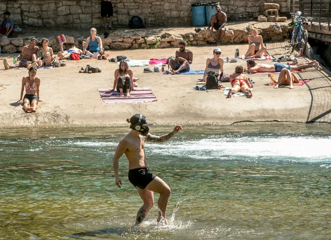 Dozens of people gathered at Barton Creek below the dam at Barton Springs Pool on the first day of pandemic-related shelter-in-place orders in March earlier this year.