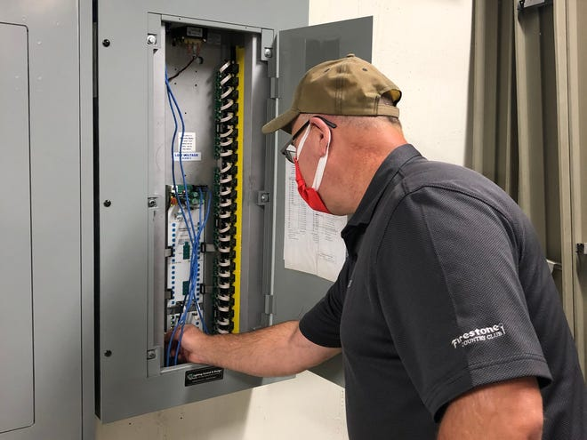 Gardiner Service Co. Engineer Mark Ludrosky examines the lighting control system at Green's Central Administration Building. Green City Council has approved a 10-year, $1.14 million efficiency program through Gardiner that is designed to bring down energy costs.