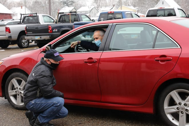 University of Mount Union's Physical Plant director Blaine Lewis kneels beside a car that was part of a parade of well-wishers Thursday that marked Lewis' impending retirement.