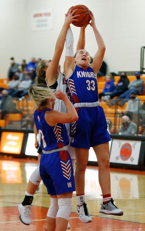 West Holmes' Katie Sprang (33) and Ashland High's Kaylee Friesen (30) battle for a rebound during girls basketball action Thursday at Arrow Arena. The Knights defeated the Arrows, 68-27.
