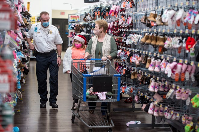 Columbia County Fire Rescue Battalion Chief Anthony Lovett, left, and Renee Peloquin, right, shop for some shoes with Graicee (cq) Harvey, 8, at the Walmart in Evans, Ga., Friday afternoon December 18, 2020.