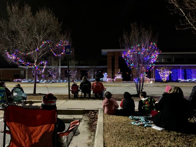 Families sit in front of Baker Place Elementary on Thursday night to watch a student-made Christmas lights show.