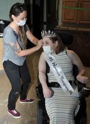 Ashley Baker, left, of Girard, Ohio, tends to some last-minute primping on Mandy McCoy's hair before her photo shoot. During the Ms. Wheelchair Pennsylvania process, Mandy told a panel of judges in writing that she wanted to help young people with disabilities make the transition from adolescence to young adulthood easier.