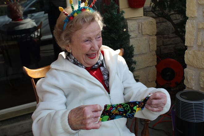 Anne Platner greets friends and neighbors who come by to wish her a happy 100th birthday.