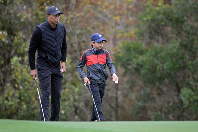Tiger Woods lines up a putt with his son Charlie on the 11th green during a practice round Thursday in Orlando, Fla.